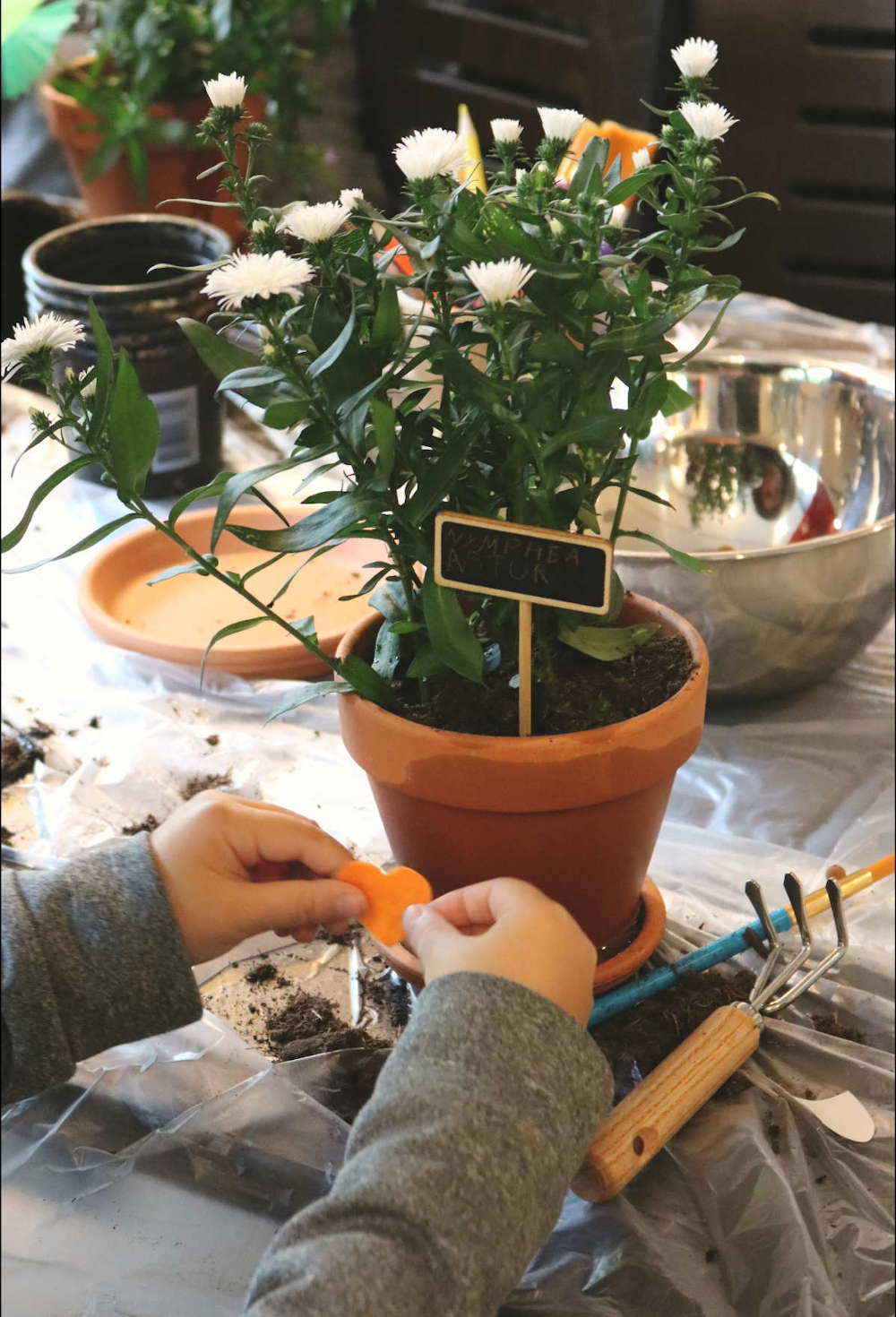 enfant entrain de décorer un pot en terre cuite, atelier jardinage